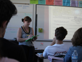 Long term French language substitute Madame Villanueva marks participation points on her clipboard during 5th period. Students must participate 5 times a week to get full credit on their participation grade.