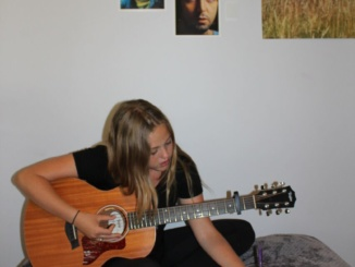Costa sophomore Jamisen Jarvis playing her guitar. She was playing one of her original songs on the guitar in her room.
