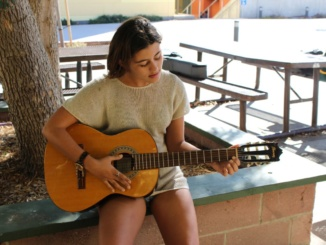 Emily Austin plays the guitar as well as also having acting roles, modeling jobs, and singing.   This phot just exhibits one of the many things she can do.