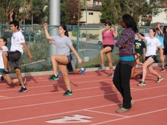 New track coach, Blessing Ufodiama finishes demonstrating a jumping drill to the Mustang athletes at Waller Stadium. Ufodiama has taught many new techniques and used her experience to benefit these beginning runners.