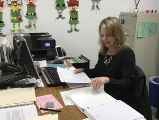 Nancy DiRado, the vice principal's secretary for the 2016-17 school year, organizes paperwork on her desk on Dec. 15. She, along with 11 other staff members, were hired by Dale for the 2016-2017 school year.