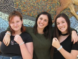 """Lilly Fuller (left), Kyra Dates (middle) and Ava Alexiades (right) protested the presidential election last November by wearing black in semblance of the country's """"funeral"""". Their bracelets are hand created by Dates and then sold to donate money to LGBTQ+ charities. Courtesy of Ryan Demarest"""