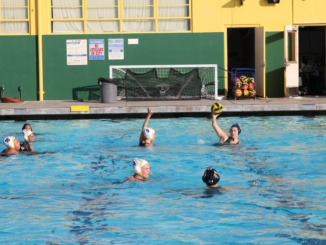 Costa (in blue caps) Senior Attacker Leigh Lyter protects the ball and searches the pool for a teammate to pass to in the early stages of the third quarter of Costa's 7-3 win. Eventually, she found Skylar Jefferson in front of the goal, which lead to another Costa goal which made the score 4-3 in Costa's favor.