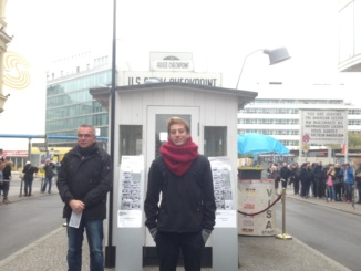 Courtesey of Aj Silverman  Aj Silverman (center) stands in front of Checkpoint Charlie in Berlin while on a Germany tour with the Rotary Student Exchange in August of 2016. Checkpoint Charlie is the name given to the Berlin Wall built in World War Two connecting East and West Germany. Silverman got to view remains of the wall, as well as enter the Checkpoint Charlie museum. Silverman's says his favorite part of his study abroad experience is his tour of Europe.