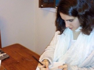 Senior Lydia Hirsch writing  her poems in the South Bay. Hirsch compiled a majority of her own poems into a book that was published in August of 2016. (Courtesy of Lydia Hirsch)
