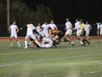 Mira Costa (White) surrounds a tackled Falcon player in an attempt to take possession on February 18. The Mustangs would eventually fall just short of a victory.