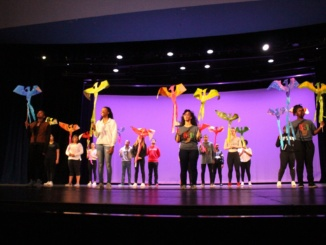 """Mira Costa's annual Black History Month Assembly, hosted by the Black Scholars Union club, was held in the auditorium during fourth period. Members of Costa's Black Scholars Union club raise paper phoenixes while Costa English teacher Shawn Chen recites the poem, """"Still I Rise"""" by Maya Angelou. The Black History Month assembly took place today in the auditorium."""