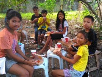 Filipino children sit in a circle while enjoying their food given to them by Costa student Raymund Avenido and his family in January in Central Philippines. Avenido said that it was a great experience to see how happy the kids were to get the food.
