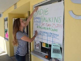 "Senior Emily Angiolini hangs a poster advertising the 2017 Mira Costa Sadie Hawkins Dance during lunch on March 9 near the East Locker Hall. ASB announced the dance, themed ""The Suite Life At Sadies,"" that will take place on March 25 at the Embassy Suites near LAX. (Brogan Tyrer/La Vista)"