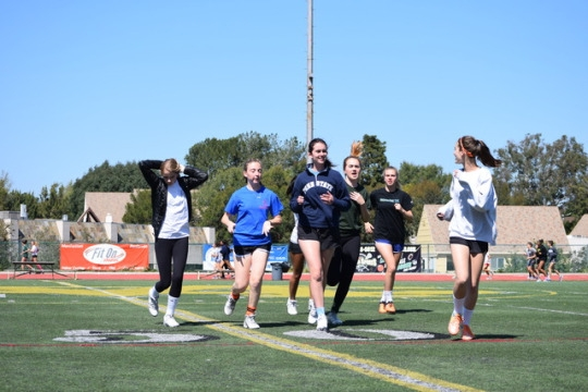 Varsity and JV girls lacrosse players warm up before practice on Friday. Their warm-up consisted of getting in six different lines, and following each girl in front of them their workout routine.