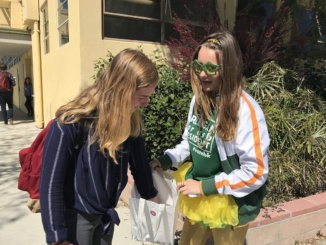 ASB Junior Vice President Breegan Knudson (right), who is running for ASB President, hands out candy to Camille Caflisch (left) in the Mustang Mall between passing periods. Knudson designed t-shirts, created pins and hung up posters throughout campus in order to gain student support before the upcoming ASB election on Wednesday.