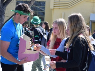 Junior Jackson Cunningham passes out donuts to his fellow junior classmates during election week. Cunningham ran for senior class vice president against three other juniors.