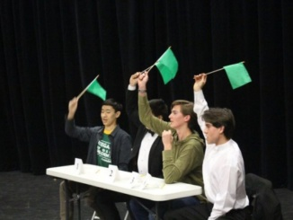 In Scholar Quiz Semi finals, Team Captain Peter Lu, Kevin Chen, Noah Geller and Tommy Kelleher all raise their flags to answer a question. Lu's team defeated their opponent and advanced to the Scholar Quiz Finals.