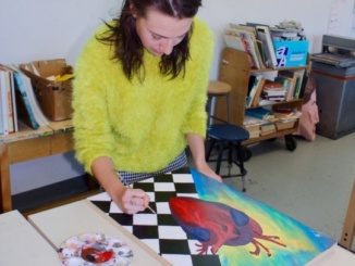 Sophomore Devon McKnight puts a few final touches on her painting at the beginning of lunch in the art room before submitting it to an upcoming art show. She began the project three weeks ago.