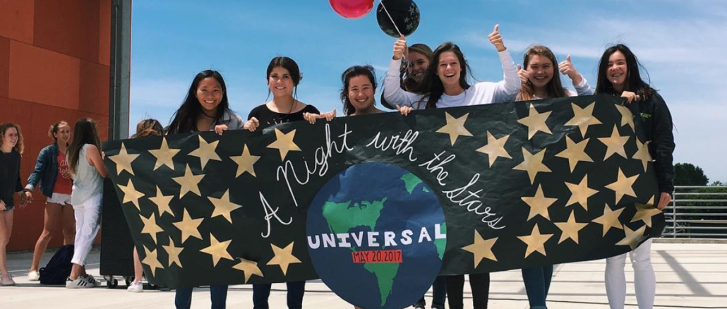 Reproduced with the permission of @asbmustangs via Instagram  Students stand on the stage in the Mustang Mall and hold a sign about Prom on Friday. The sign had been made by ASB to promote Prom.