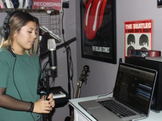 Senior Alyssa Davis sings a song in the recording studio. Since starting the internship about three months ago, Davis has met famous artists in the music industry, such as John Legend.