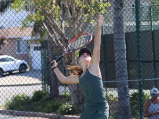 (Middle) Freshman Lucy Fiorito tosses the ball in the air and prepares her serve. Mira Costa's girls tennis team defeated Los Alamitos 13-5 at Los Alamitos on Wednesday.