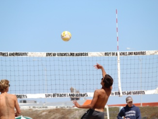 Sophomore Sam Collins spikes the ball in a game against Palisades High School on Saturday at Dockweiler Beach. He and junior Thomas Kretschmer won two sets, 27-25 and 21-14.