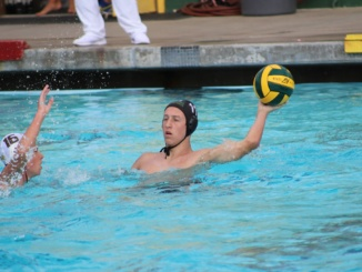 (Right) Junior attacker Holden Brown extends his arm in an attempt to pass the ball. Mira Costa's water polo team defeated Palos Verdes High School 9-8 in overtime at Palos Verdes on Wednesday.
