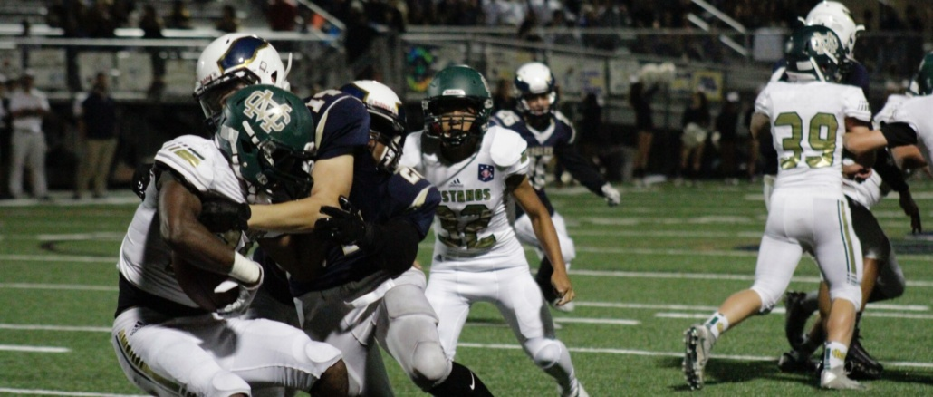 (Left) Junior Running Back Malachi McMahon forces himself through two defenders during a run play. The Mira Costa football team was defeated by El Segundo, 21-6, at El Segundo on Friday.