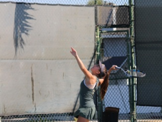 Sophomore Peyton Douglas prepares to serve the tennis ball. The Mustangs defeated Los Pueblos 13-5 on Friday.