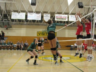 (Middle) Sophomore outside hitter Katie Colvin spikes the ball over two of the opposing team's defenders. The Mira Costa girls volleyball team was defeated by Mater Dei Highschool, 3-1, at Mater Dei in the second round of CIF playoffs on Thursday.