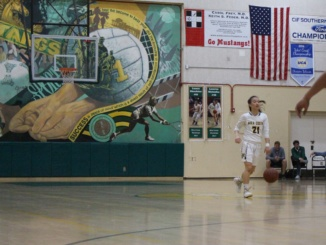 In a game last year,  Kelli Toyooka dribbles the ball up the floor. On Monday, Dec. 11, the Mustangs played Cypress High School and lost by 1.